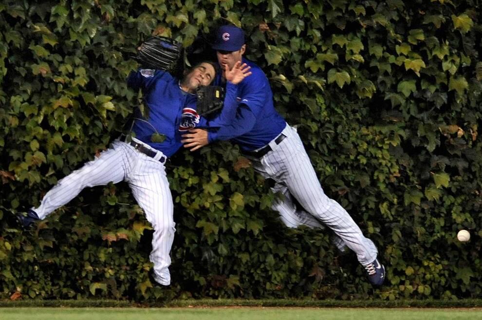 15) Игроки в дальней части поля из команды «Chicago Cubs» Мика Хофпауир, слева, и Сэм Фалд столкнулись, пытаясь поймать подачу игрока «Pittsburgh Pirates'» Эндрю МакКатчеса в первом иннинге во время игры в бейсбол на «Wrigley Field» в Чикаго 30 сентября. (Paul Beaty/AP)