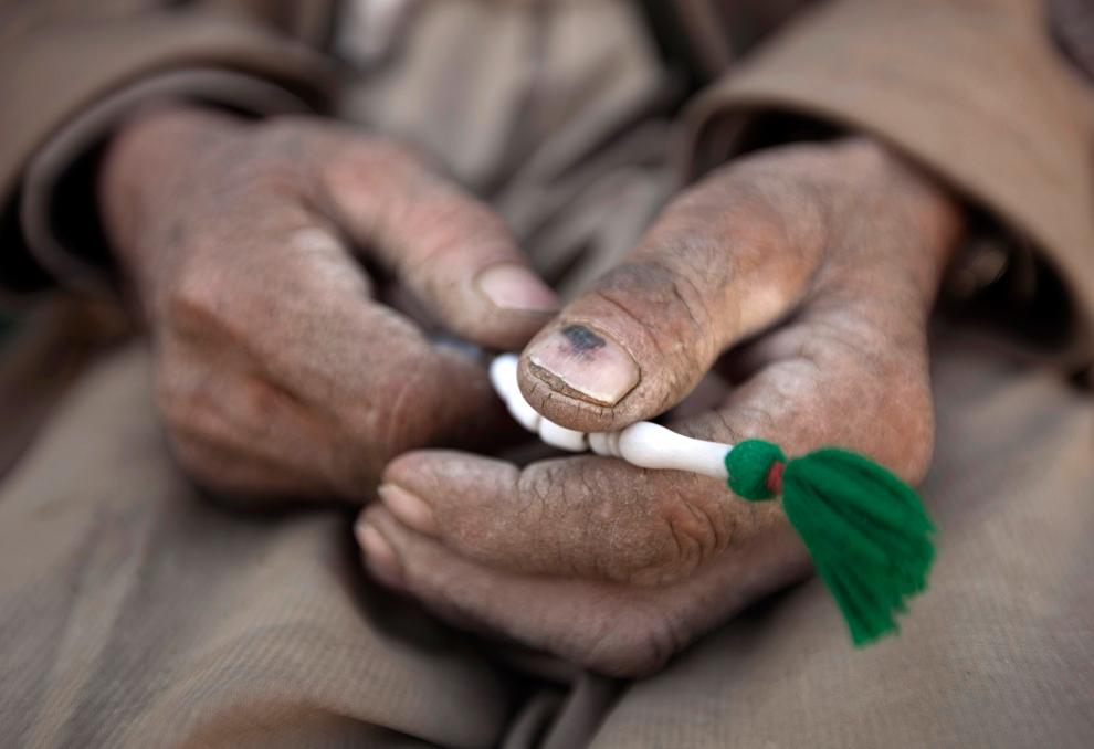 1. Афганский плотник держит четки, стоя перед магазинчиком в Кабуле 19 октября 2009 года. (REUTERS/Ahmad Masood)