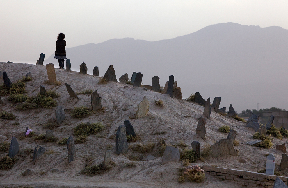 2. Афганская девочка стоит на холме на кладбище. 19 октября 2009 года в Кабуле Независимая Избирательная комиссия с поддержкой ООН объявила долгожданные результаты президентских выборов, проведенных еще в августе. Афганская Избирательная комиссия по жалобам заявила, что процент голосов за президента Хамида Карзая упал до 48 процентов из-за того, что бюллетени 210 избирательных участков не были учтены при подсчете голосов в результате обвинений в подтасовке и обмане. Представители комиссии утверждают, что именно этих голосов и не хватило Хамиду Казаю, чтобы опередить своего главного соперника Абдуллу Абдуллу. (Paula Bronstein /Getty Images)