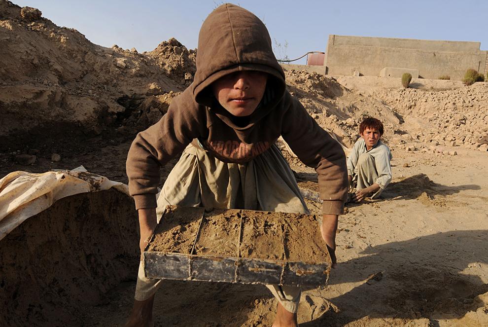 4. На этом снимке, сделанном 18 октября 2009 года, 13-летний афганский мальчик Амин (справа) и его 12-летний брат Таза делают кирпичи на окраине Кабула. Кирпичи, которые тысячами  аккуратно изготовливаются здесь, пользуются высоким спросом в столице и по всему Афганистану, так как страна пытается восстановиться после 30-летнего конфликта. (SHAH MARAI/AFP/Getty Images)