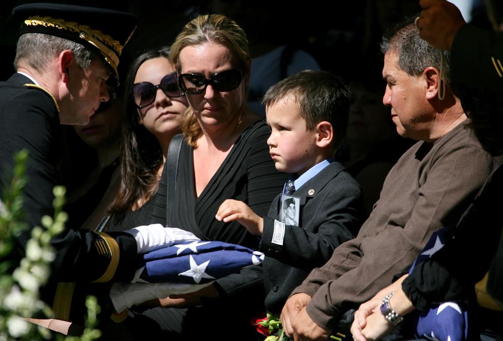 5. 5-летний МакЭйдан Галлегос получает флаг из рук бригадного генерала Шона МакФарланда на глазах своей матери Аманды Дойл на кладбище в Туксоне, штат Аризона, 15 октября 2009 года. Мальчик приходится сыном погибшему сержанту Джастину Галлегосу, который был одним из восьми солдат, погибших в Афганистане 3 октября 2009 года во время перестрелки с боевиками в отдаленном регионе на пакистанской границе. (AP Photo/Arizona Daily Star, Mamta Popat)
