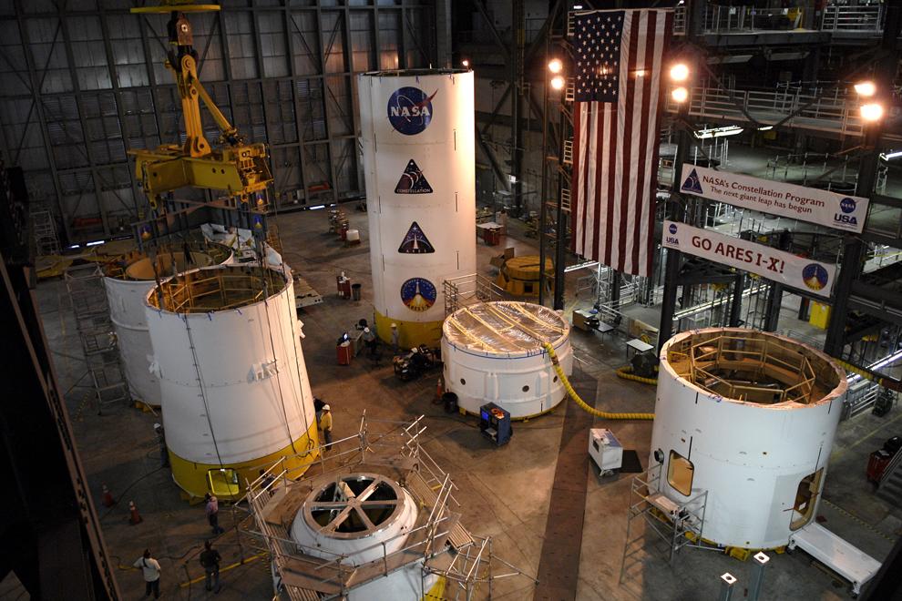 8. Верхнюю ступень Ares I-X симулятора служебного модуля/модуля адаптации (слева в центре) устанавливают на стенд в отделении High Bay 4 корпуса сборки кораблей на космодроме Кеннеди во Флориде. Другие составляющие помещаются и стыкуются на полу вокруг него. Ares I-X – испытательный аппарат для ракеты Ares I, которая входит в программу «Созвездие» для возвращения людей на луну и дальше. (NASA/Kim Shiflett)