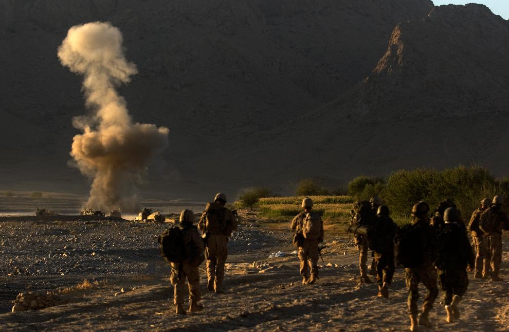 13. Пехотинцы из второго батальона третьего пехотного полка, а также солдаты из Афганской национальной полиции патрулировали территорию, когда вдалеке сдетонировало самодельное взрывное устройство. Снимок сделан в неспокойной провинции Фарах 10 октября 2009 года. (DAVID FURST/AFP/Getty Images)