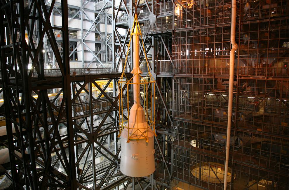 14. Сбор ракеты Ares I-X  в корпусе по сборке аппаратов практически завершен. Желтый каркас под кодовым названием «клетка» поднимает связку Super Stack 5 к открытому пространству на 16 этаже. Связка будет помещена сверху на сегменты, уже установленные на мобильной платформе запуска в отсеке High Bay 3, что и завершит сбор 99-метровой ракеты. Пять супер связок составляют верхнюю ступень ракеты, встроенной в твердотопливный ускоритель первой ступени. (NASA/Dimitri Gerondidakis)