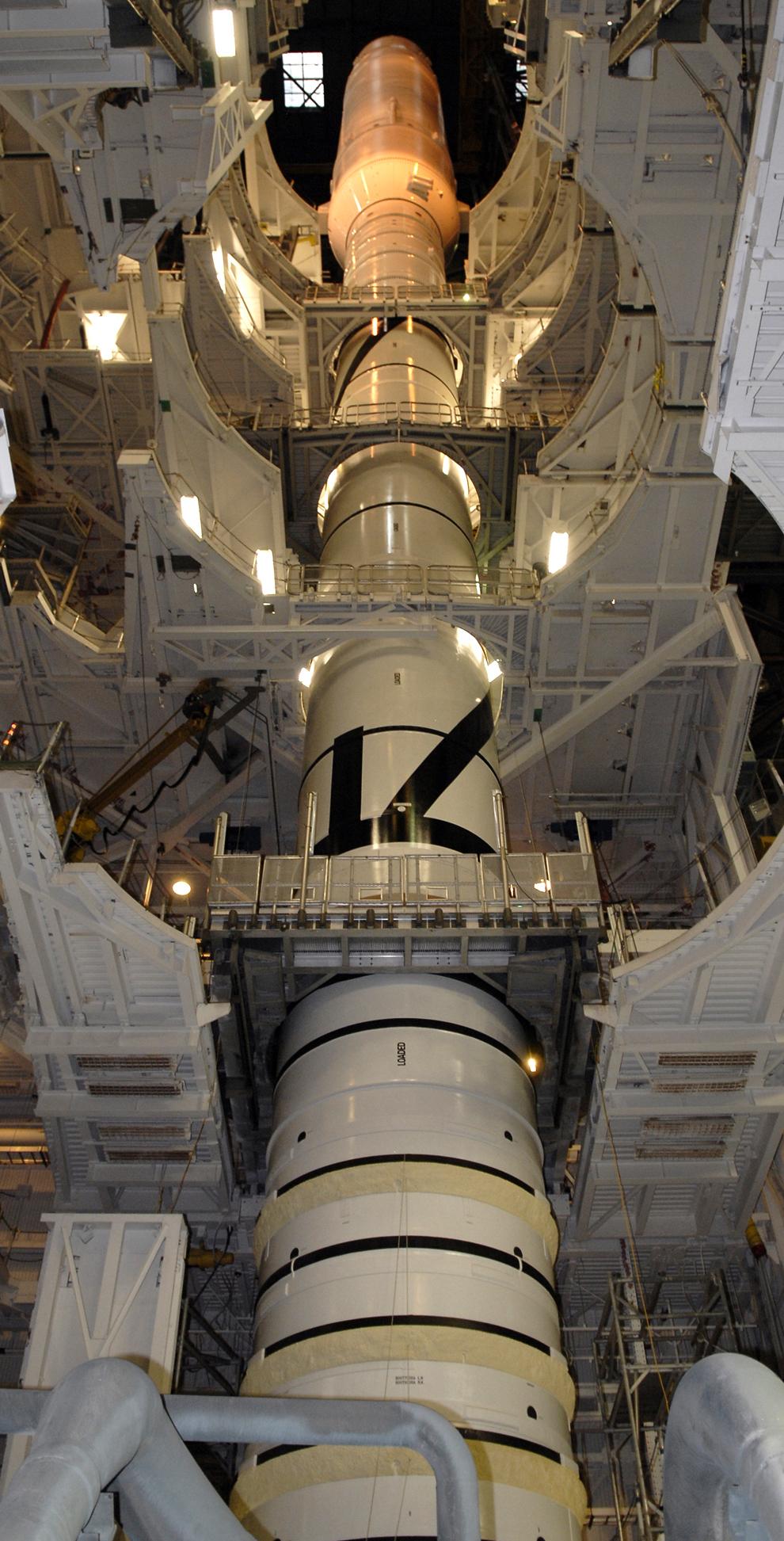 16. Рабочие площадки окружают ракету Ares I-X в корпусе по сбору аппаратов в космическом центре Кеннеди. Ракета прошла тестирование в условиях, в которых она может оказаться во время выхода из крена на стартовой площадке 39B, а также погодных условиях на платформе и первый запуск. Во время тестирования четыре штановых стряхивателя с гидроприводом доставляют вибрации в ракету, и колебание поперечного движения вводится в ручную, чтобы измерить отдачу летательного аппарата. На испытательном аппарате установлено в общей сложности 44 акселерометра, на это потребовалось более 8 222 метров кабеля. (NASA/Kim Shiflett)