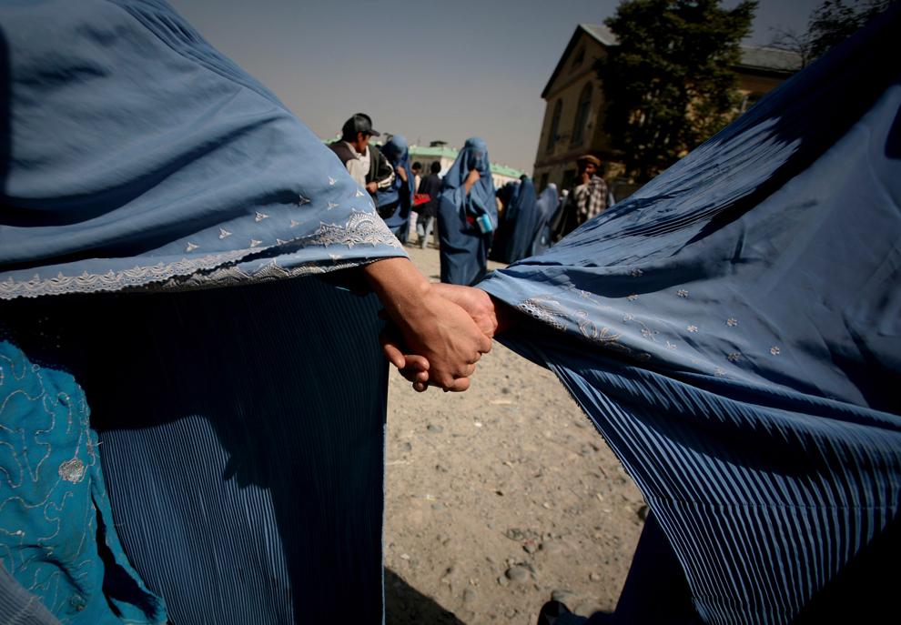 17. Две афганские женщины держатся за руки на рынке в Кабуле 20 октября 2009 года. (AP Photo/Altaf Qadri)