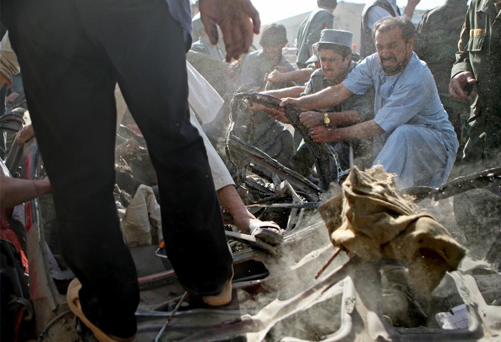 18. Спасатели достают тело на месте взрыва 8 октября 2009 года в Кабуле. В результате взрыва террористов-смертников погибло 12 человек и более 60 получили ранения. Как считают местные власти, теракт был направлен на индийское посольство в Кабуле. (David Goldman/Getty Images)