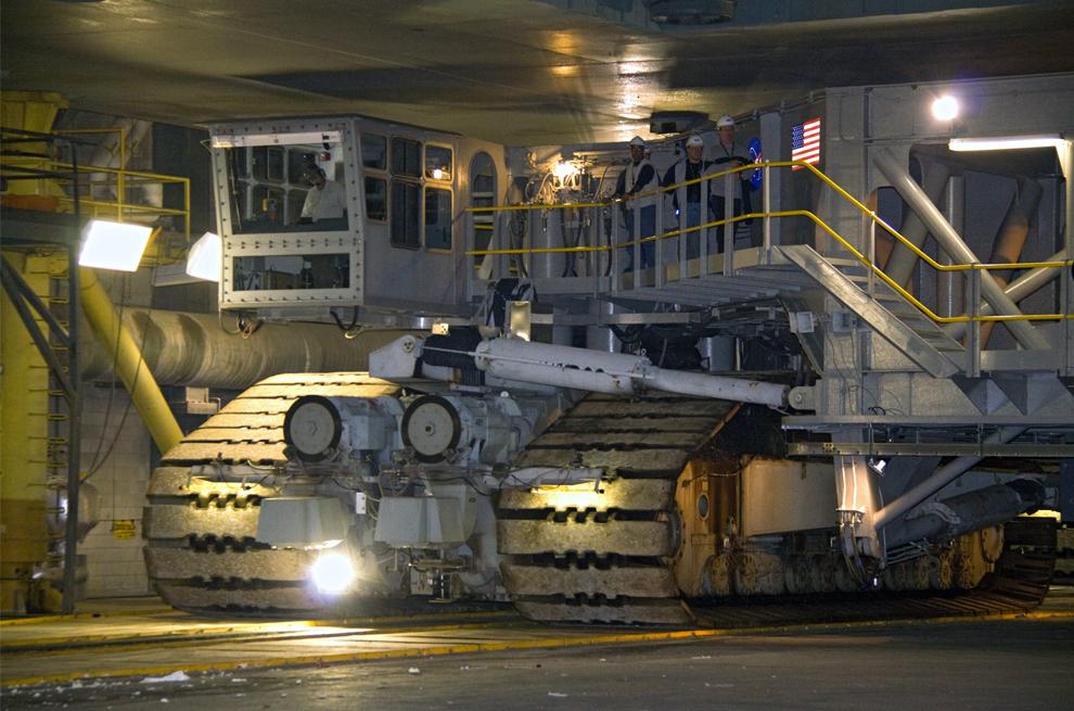 20. Водитель гусеничного транспортера осторожно управляет огромным аппаратом под мобильной стартовой площадкой с 99-метровой ракетой Ares I-X в космическом центре Кеннеди во Флориде. Гусеничный транспортер доставит ракету на стартовую площадку 39B. Передача площадки от программы «Space Shuttle» программе «Созвездие» произошло 31 мая. Среди прочих изменений площадки – удаление уникальных подсистем шаттла, таких как стрела для доступа и вентиляционный отсек газообразного кислорода, а также установка трех 182-метровых вышек, платформ доступа, систем контроля окружающей среды и системы стабилизации аппарата. (NASA/Jack Pfaller)
