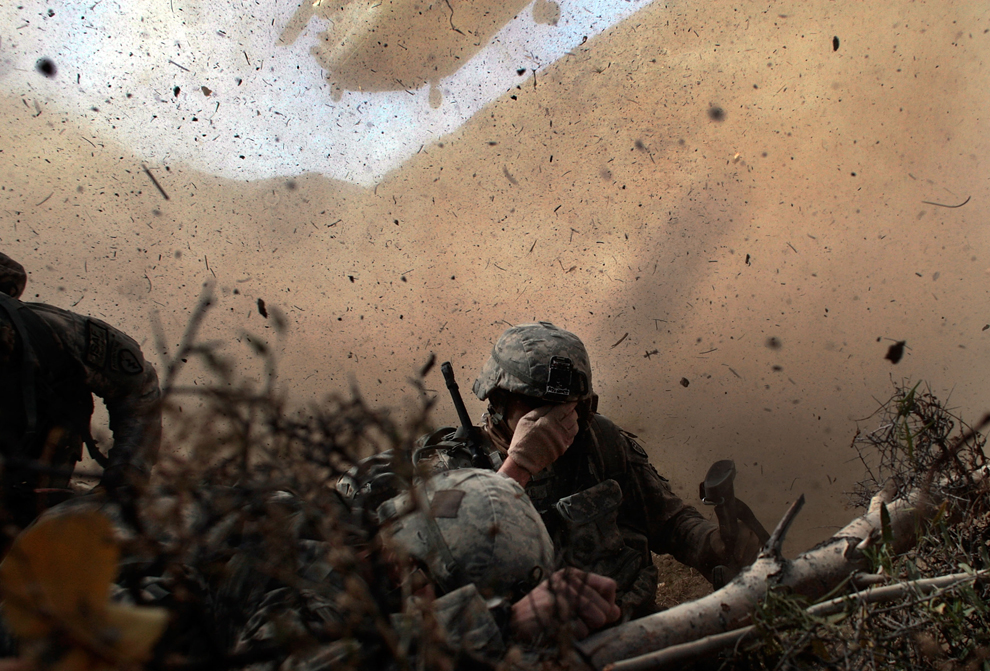 23. Солдаты армии США из 25-ой пехотной дивизии прикрывают лица от пыли и грязи, поднятых в воздух грузовым вертолетом «Chinook», который прилетел за ними. Снимок сделан 15 октября 2009 года в провинции Пактика. (Chris Hondros/Getty Images)