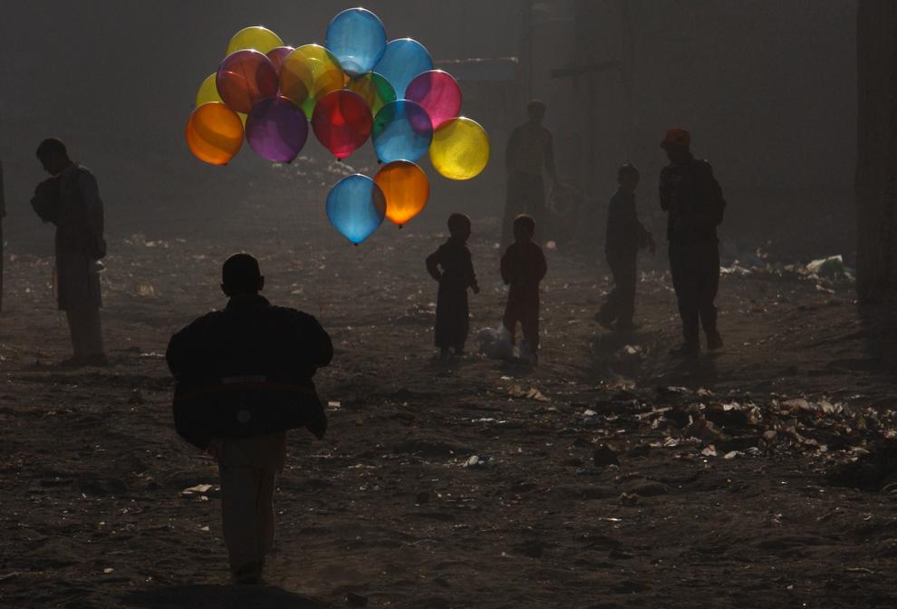 26. Афганский мальчик бежит с воздушными шариками по пыльной улице Кабула 25 октября 2009 года. (AP Photo/ Gemunu Amarasinghe)