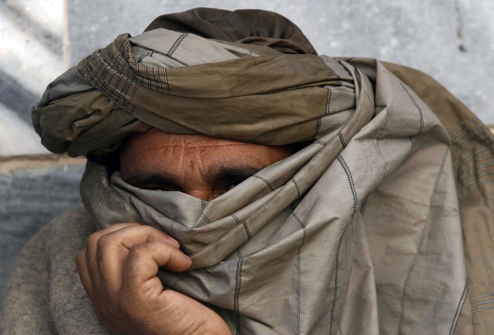 33. Бывший боевик организации «Талибан» закрывает лицо во время церемонии передачи оружия афганскому правительству в провинции Герат к западу от Кабула 14 октября 2009 года. Около 50 боевиков организации «Талибан» передали свое оружие во время программы по установлению мира. (AP Photo/Fraidoon Pooyaa)