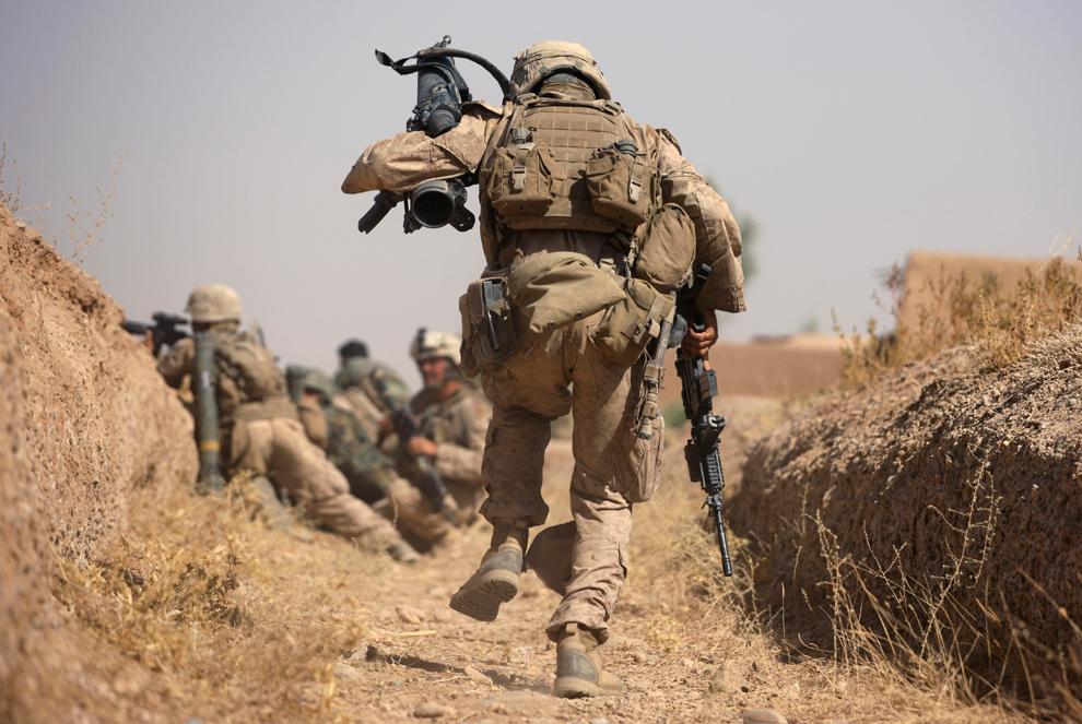 34. Младший капрал Джордан Кристи из первого батальона бежит по оросительному каналу во время перестрелки с боевиками «Талибана», чтобы установить гранатомет. Снимок сделан в округе Нава, провинция Гильменд, 4 октября 2009 года. Боевики «Талибана» напали на солдат во время патрулирования, используя автоматы, пулеметы и снайперские винтовки. (AP Photo/Brennan Linsley)