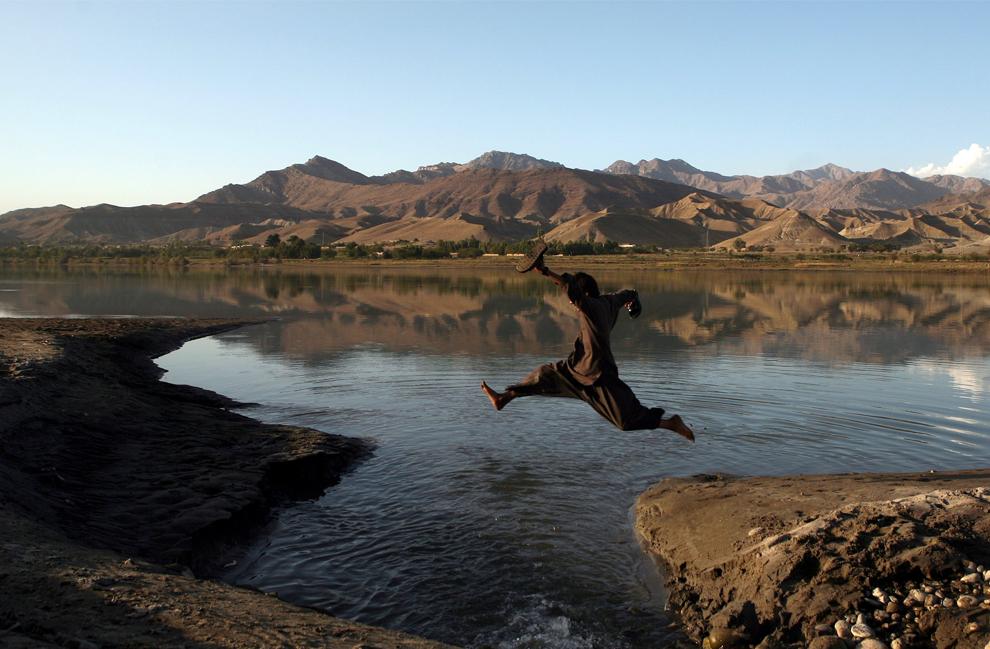 42. Афганский мальчик перепрыгивает через ручей в Сурабхи в 100 км от Кабула 7 октября 2009 года. (AP Photo/Altaf Qadri)