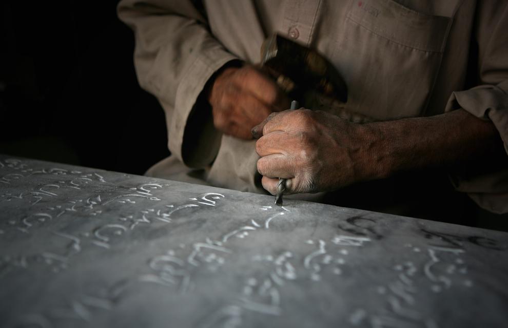 43. Мохаммад Даву, зарабатывающий тем, что гравирует имена на могилах, работает в своей мастерской на окраине Кабула 2 октября 2009 года. (AP Photo/Altaf Qadri)