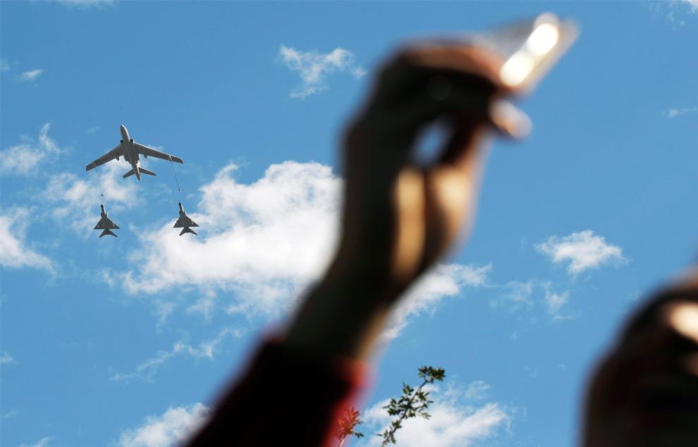22. Мужчина фотографирует истребители народно-освободительной армии на национальном празднике в Пекине 1 октября 2009 года. (LIU JIN/AFP/Getty Images)