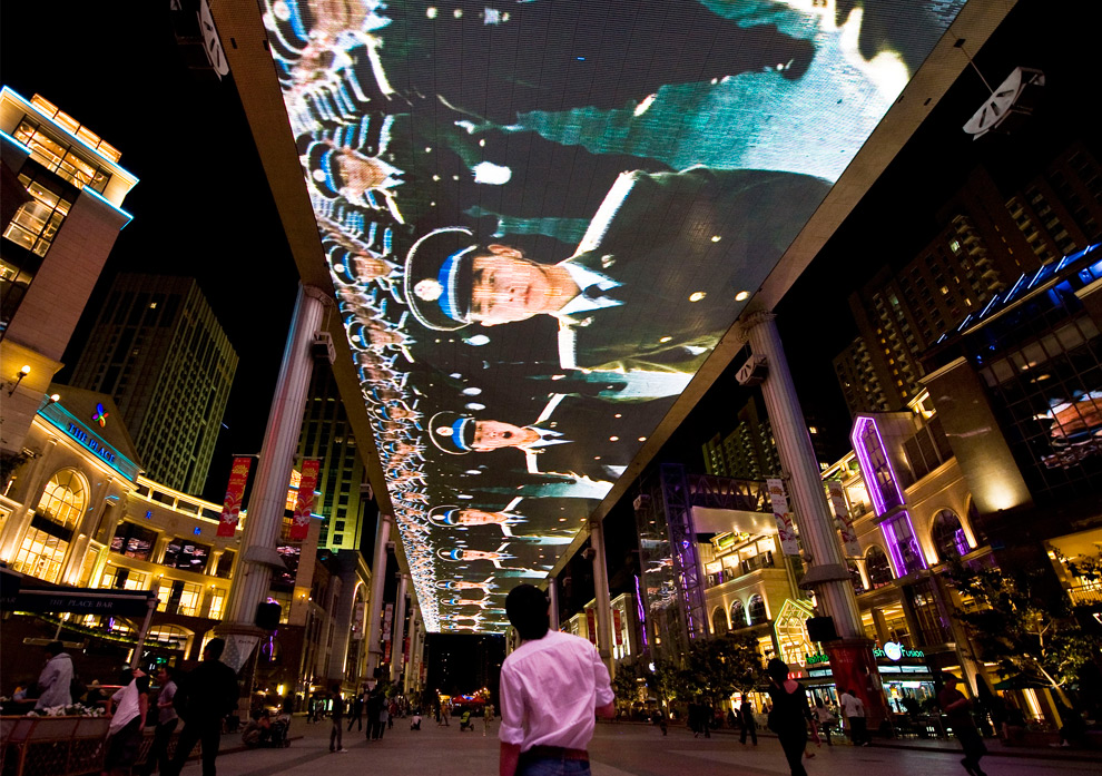 35. Мужчина смотрит на марширующих солдат народно-освободительной армии на огромном экране над головой, в торговом центре Пекина в четверг 1 октября 2009 года. (AP Photo/Andy Wong)