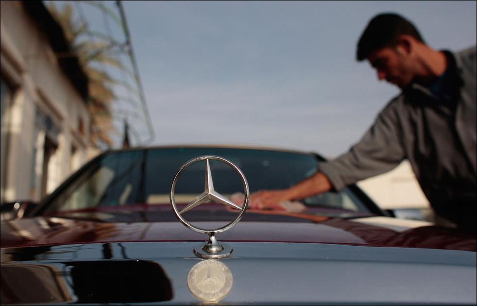 1) Сотрудник вытирает кузов Мерседеса на распродаже новых автомобилей в Багдаде. (Getty Images/Chris Hondros)