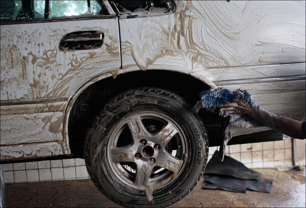 2) Житель Ирака моет автомобиль одной из последних моделей на автомойке в Багдаде. Несколько лет назад иракцы предпочитали не садиться за руль новых автомобилей из боязни того, что их повредят или уничтожат во время уличных расправ. (Getty Images/Chris Hondros)