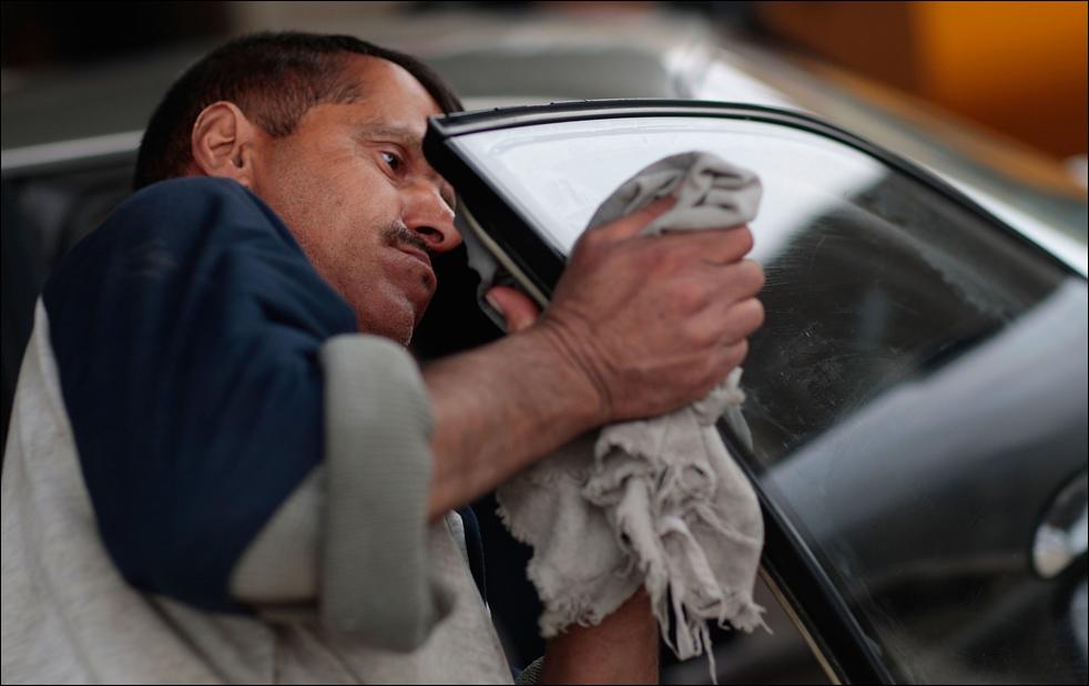 3) Работник иракской автомойки вытирает окно автомобиля последней модели в Багдаде. (Getty Images/Chris Hondros)