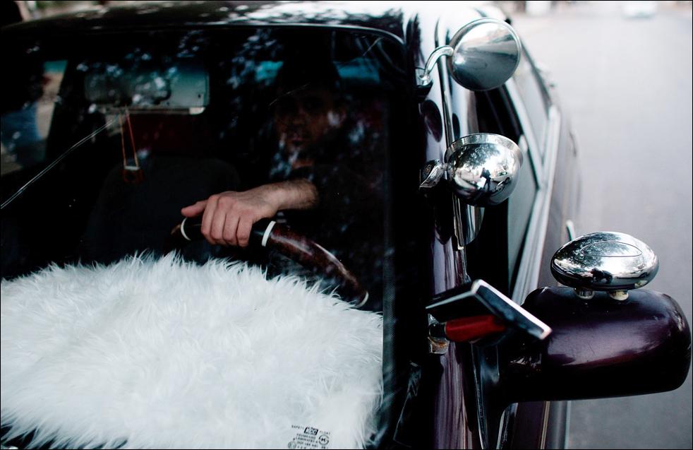 11) Иракец сидит за рулем своего тюнингованного автомобиля с добавленными зеркалами и приборной панелью покрытой искусственным мехом. (Getty Images/Chris Hondros)