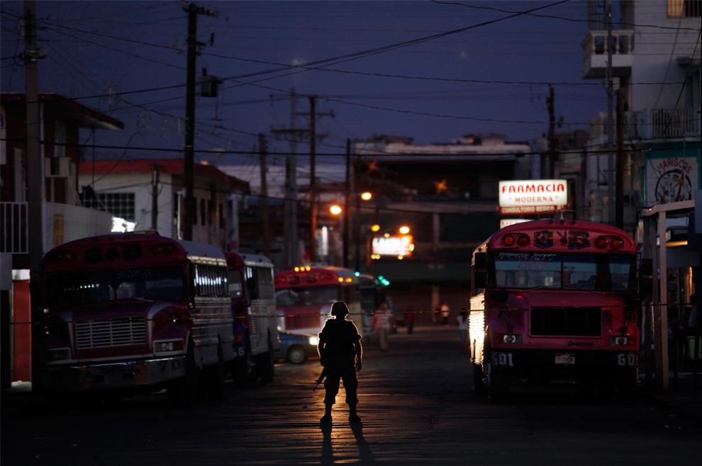 2. Солдат стоит на страже на месте преступления, где убили человека, в центре Сьюдад-Хуареса, северная Мексика, в воскресенье 13 сентября 2009 года. (AP Photo/Guillermo Arias)