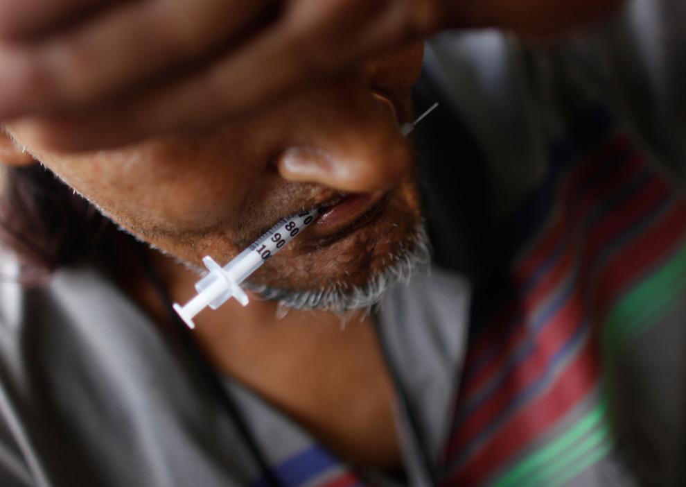 4. Наркоман держит во рту использованный шприц после укола героина в Сан-Хуане в пятницу 31 июля 2009 года. Трафик героина из Южной Америки проходит через Пуэрто-Рико в США. Продажа здесь героина привела к распространению эпидемии. (AP Photo/Brennan Linsley)