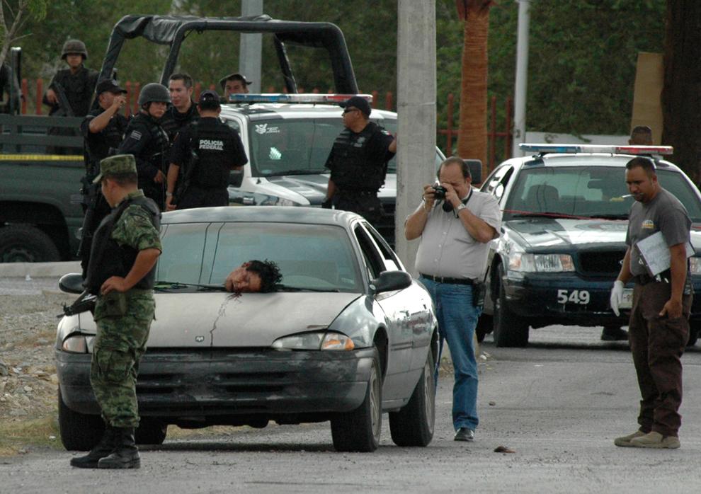 5. Оторванная голова неопознанного мужчины лежит на капоте автомобиля на месте преступления, произошедшего на окраине Хуареса, Мексика, в субботу 8 августа 2009 года. Согласно полиции, оставшаяся часть тела жертвы была найдена в багажнике. (AP Photo/Reymundo Ruiz)