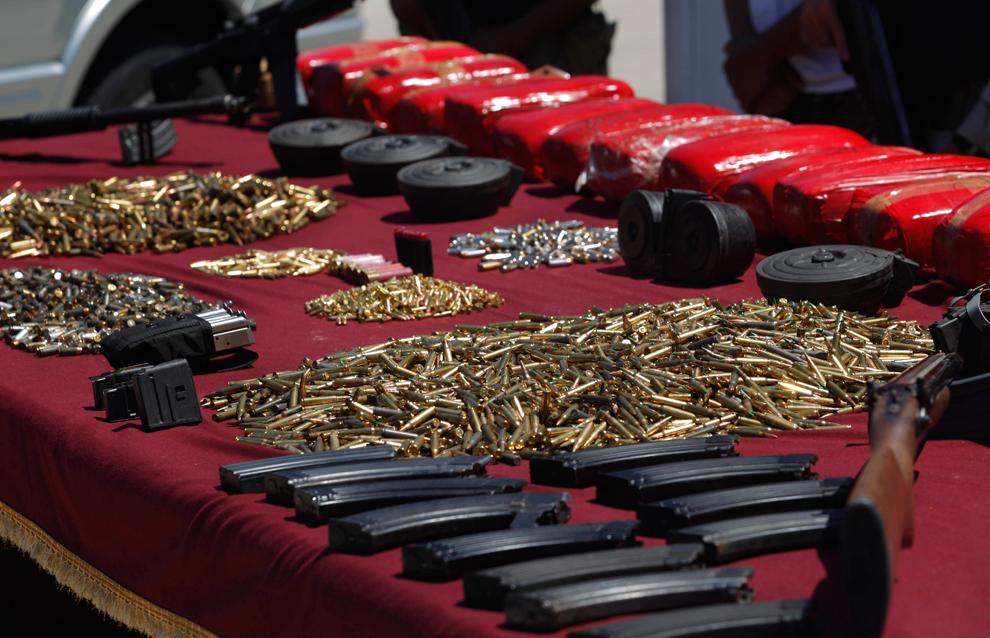 10. Конфискованное оружие, гильзы, магазины и марихуана выложены перед репортерами в Тихуане, Мексика, в среду 5 августа 2009 года. (AP Photo/Guillermo Arias)