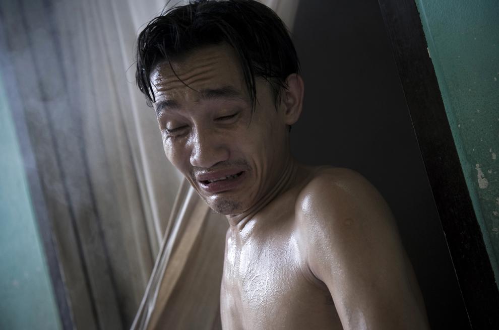 13. На этом снимке, сделанном 3 июля 2009 года, тайский наркоман выходит из комнаты, наполненной травяными парами, в монастыре Тамкрабок в Фрапуттхабате в 140 км к северу от Бангкока. Постоянно увеличивающееся число наркоманов и алкоголиков – как из Таиланда, так и из других стран – посещают центр реабилитации в монастыре Тамкрабок. Другие традиционные способы лечения своей зависимости они не нашли. (NICOLAS ASFOURI/AFP/Getty Images)
