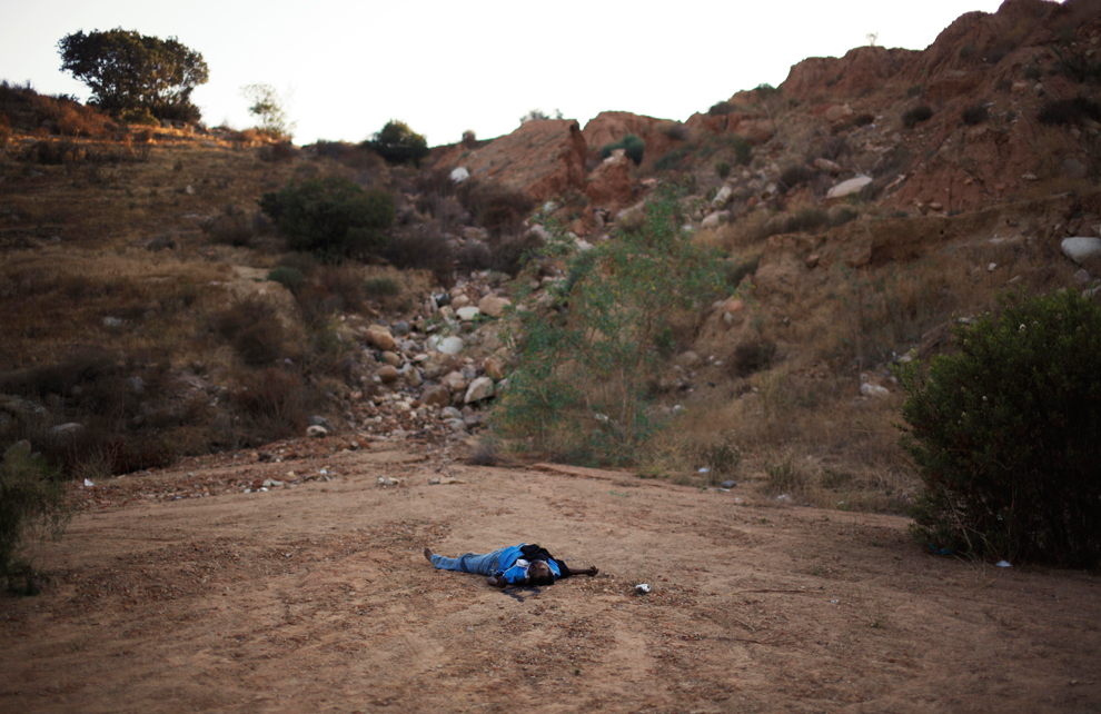 14. Мертвец на дороге на окраине Тихуаны, Мексика, в среду 12 августа 2009 года. Мужчина был найден с пулей в голове. (AP Photo/Guillermo Arias)