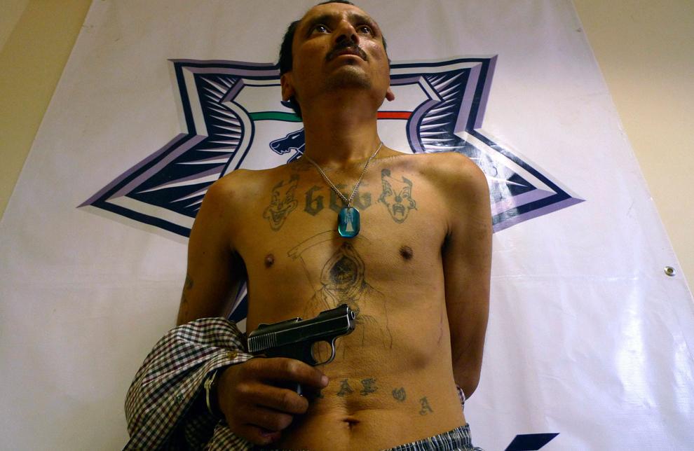 18. 37-летний Гваделупе Вазкез в наручниках перед репортерами. Он держит незаряженный пистолет, который он использовал во время столкновения с федеральной полицией во вторник в Тихуане, Мексика, 6 октября 2009 года. (AP Photo/Guillermo Arias)