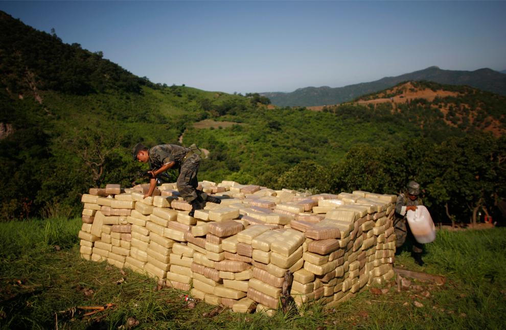21. Мексиканские солдаты готовятся сжечь пакеты с марихуаной во время операции недалеко от секретной нарколаборатории в Тамазуле, Мексика, в понедельник 10 августа 2009 года. Согласно федеральным властям, лаборатория была оснащена оборудованием, достаточным для производства одной тонны метамфетамина каждую неделю. (AP Photo/Miguel Tovar)