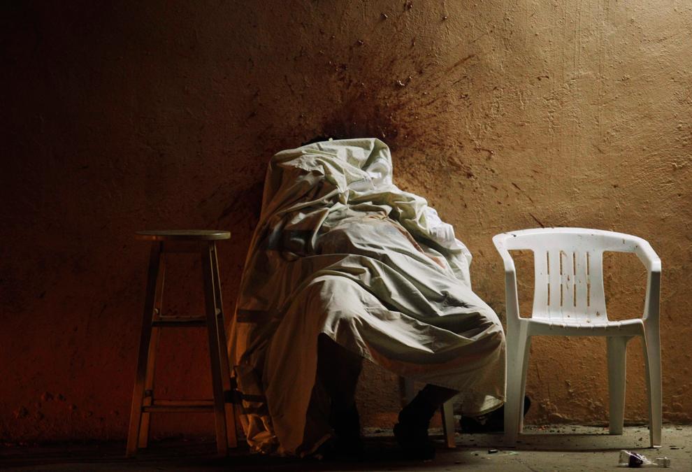 29. Окровавленная стена и тело наркодилера закрытое простыней. Его убили прямо перед его домом в Тихуане, Мексика, вечером в воскресенье 6 сентября 2009 года. (AP Photo/Guillermo Arias)