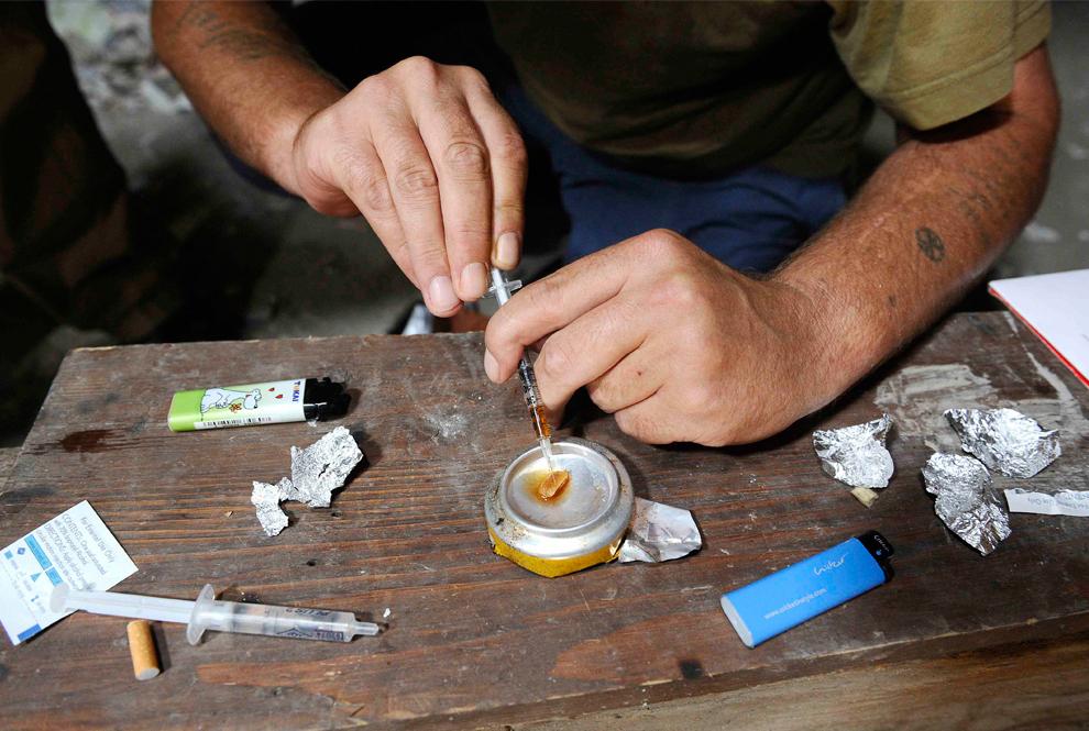 31. Человек готовит дозу героина в заброшенном доме в Любляне 3 августа 2009 года. (REUTERS/Bor Slana)