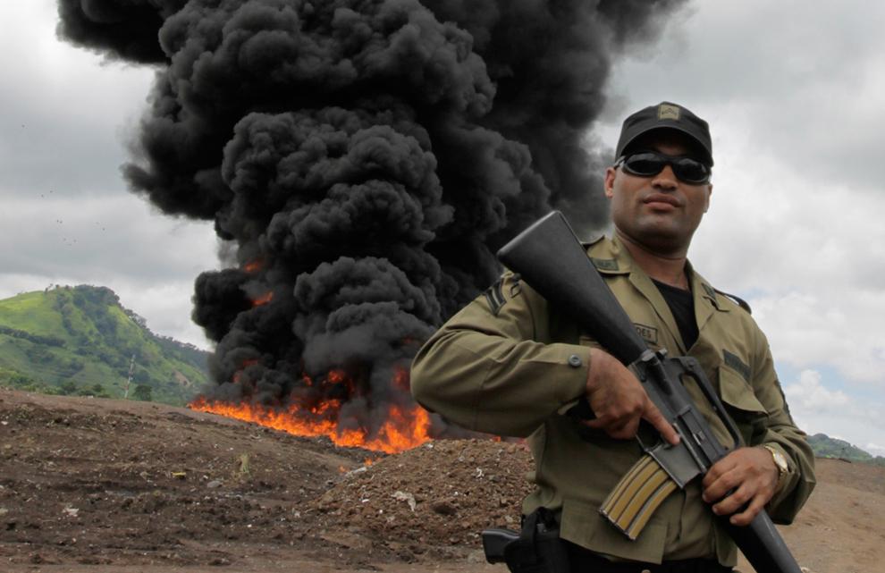 34. Офицер полиции стоит на страже, в то время как на заднем плане горят наркотики. Снимок сделан в Панаме 31 июля 2009 года. Власти уничтожили более шести тонн кокаина и марихуаны, конфискованных в июне и июле. (REUTERS/Alberto Lowe)