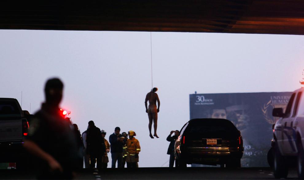 35. Тело неопознанного человека висит под мостом на старом шоссе Розарито в Тихуане, Мексика, в пятницу 9 октября 2009 года. Полиция нашла мужчину голым, избитым и кастрированным. Его еще не опознали, но власти предполагают, что это Рогелио Санчес – представитель правительственных органов Калифорнии, пропавший на прошлой неделе. Подозреваемых пока не называли. (AP Photo/Guillermo Arias)