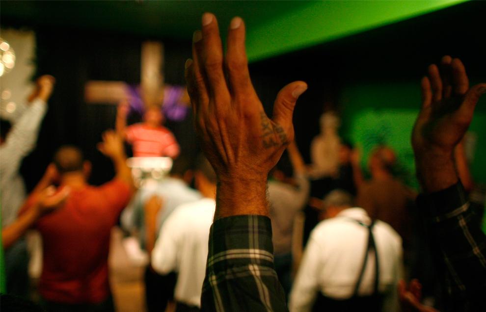 37. Излечившийся от героиновой зависимости мужчина поднимает руки во время молитвы в министерстве в пограничном городе Сьюдад-Хуарес 9 сентября 2009 года. Министерство помогает наркоманам, алкоголиками и проституткам изменить жизни к лучшему с помощью молитв. В прошлом на реабилитационные центры нападали банды наркодельцов, обвиняя их в укрывательстве наркоторговцев из конкурирующих банд. (REUTERS/Tomas Bravo)