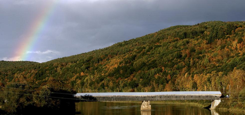 19. Радуга над крытым мостом, соединяющим Уинсдор, штат Вермонт (слева), и Корниш, Нью-Хэмпшир, на фоне меняющей цвет осенней листвы в понедельник 5 октября. (AP / Jim Cole)