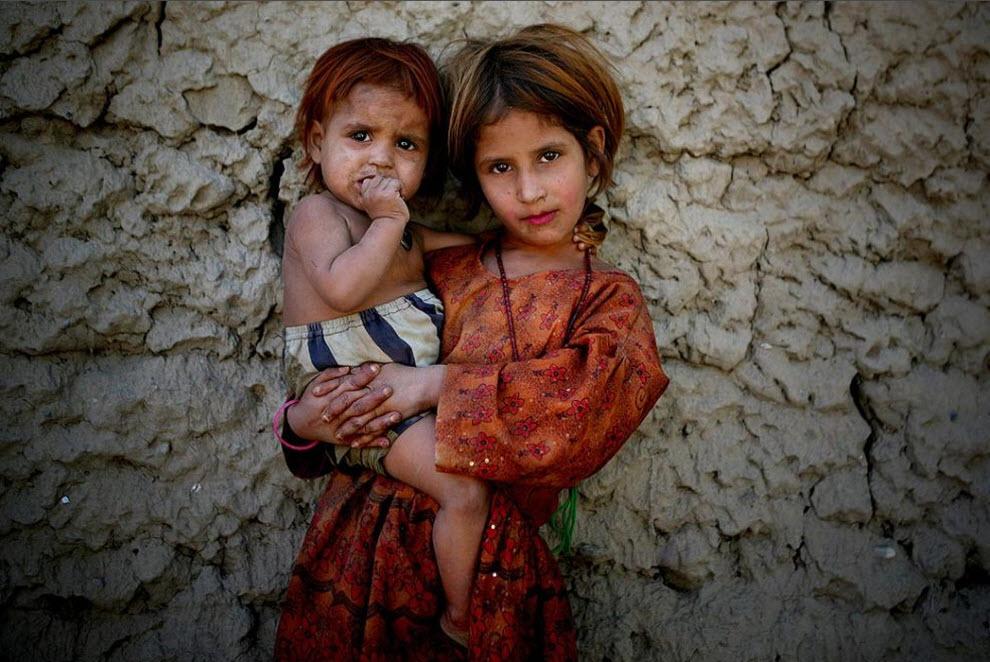 9) Зубайда, афганская девочка, держит свою младшую сестренку, позируя фотографу в Джелалабаде, провинция Нангархар, к востоку от Кабула. (Altaf Qadri, AP)
