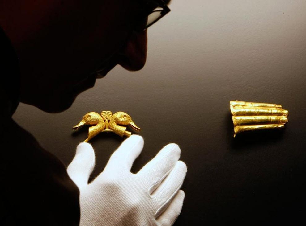 """3) Работник хранилища Мориц Пайсан показывает ценности, которым более 3 тысяч лет: две утиные головы сделанные из чистого золота и золотая рука. Эти ювелирные изделия являются частью экспозиции под названием """"Сокровища древней Сирии - открытие Королевства Катна"""" в Штутгарте, Германия. Выставка продлится с 17 октября до 14 марта 2010 года. (Томас Kienzle, AP)"""