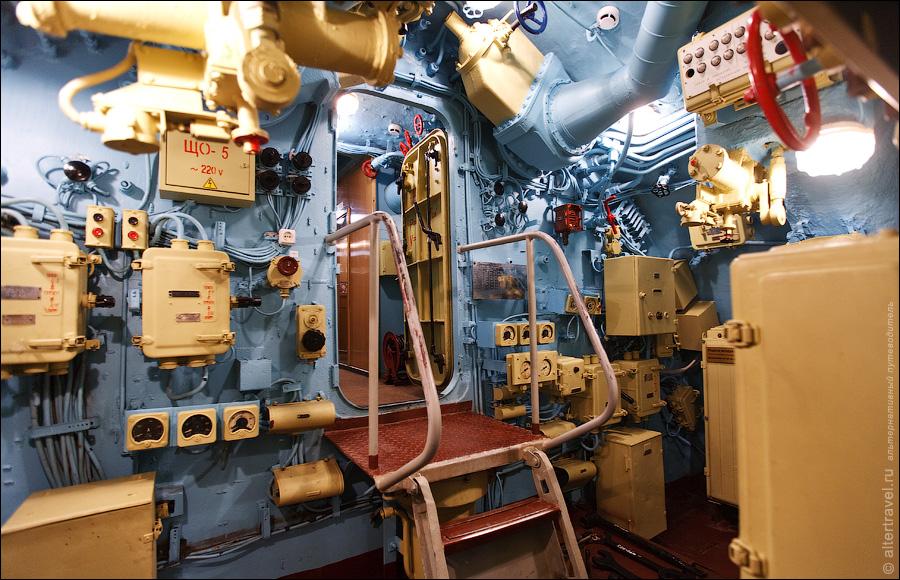12) Кормовые торпедные аппараты. Здесь же рядом располагаются койки для экипажа — в три яруса, каждая койка на трех человек в три смены.
