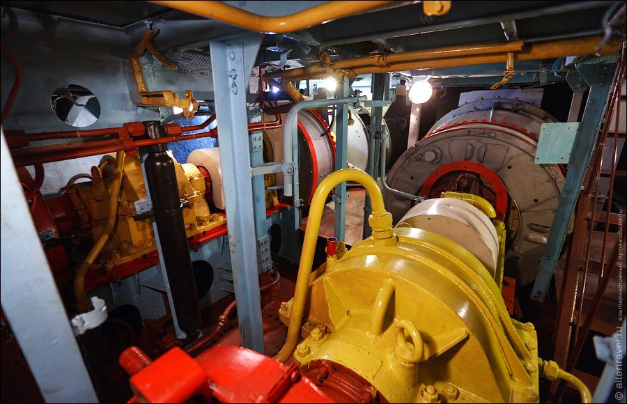 13) Кормовые торпедные аппараты. Здесь же рядом располагаются койки для экипажа — в три яруса, каждая койка на трех человек в три смены..