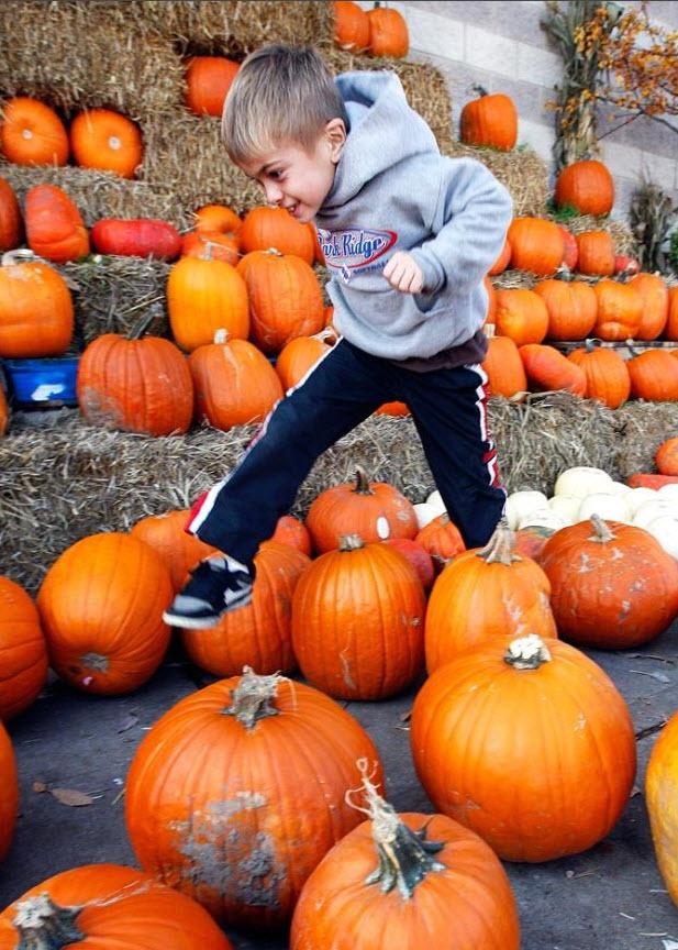 15. Мальчик прыгает через тыквы на рынке «Fresh Farms» в Чикаго 18 октября. (Nam Y. Huh, AP)