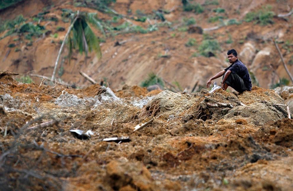 1. Выживший после землетрясения сидит на руинах уничтоженной оползнем деревни; оползень был вызван землетрясением, которое ударило по Капало Кото в Париамане, провинция Западная Суматра, 5 октября 2009 года. (REUTERS/Nicky Loh)