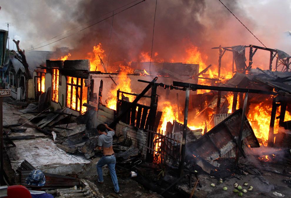 3. Мужчина пробегает мимо горящих домов после мощного землетрясения в Паданге, Западная Суматра, Индонезия, 30 сентября 2009 года. (AP Photo)
