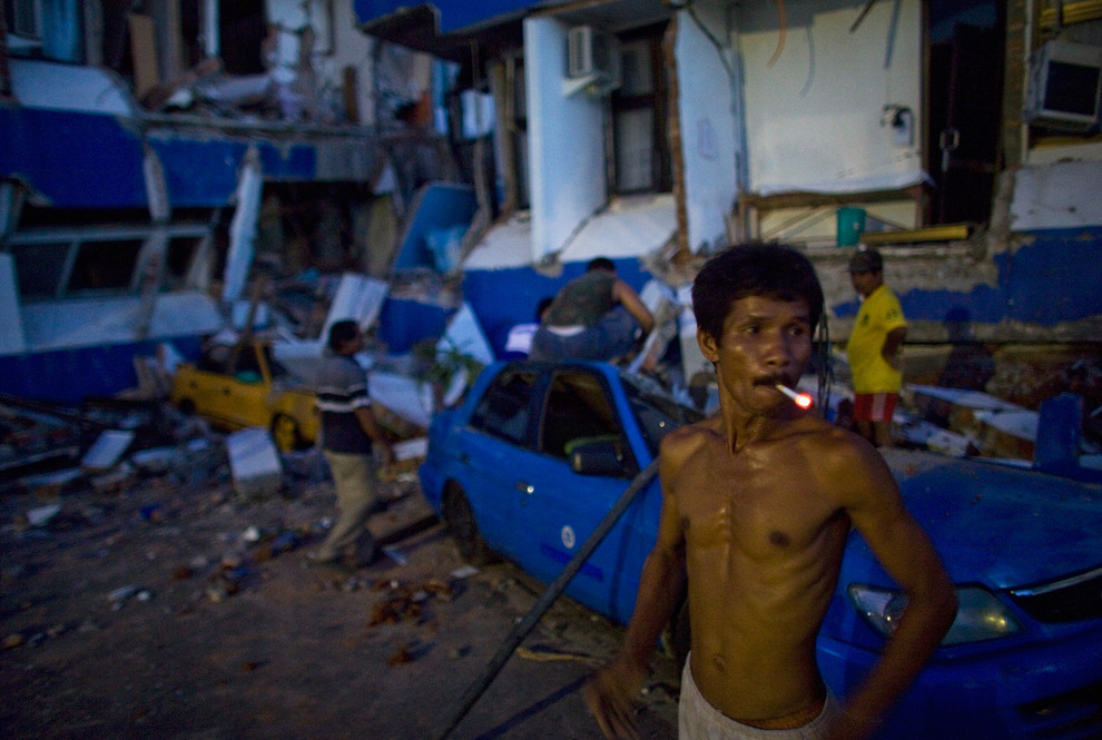 4. Рабочий решил сделать перекур, пока его коллеги продолжают разбирать машину, застрявшую под обломками, у больницы М. Джамиль 2 октября 2009 года в Паданге, Индонезия. (Daniel Berehulak/Getty Images)