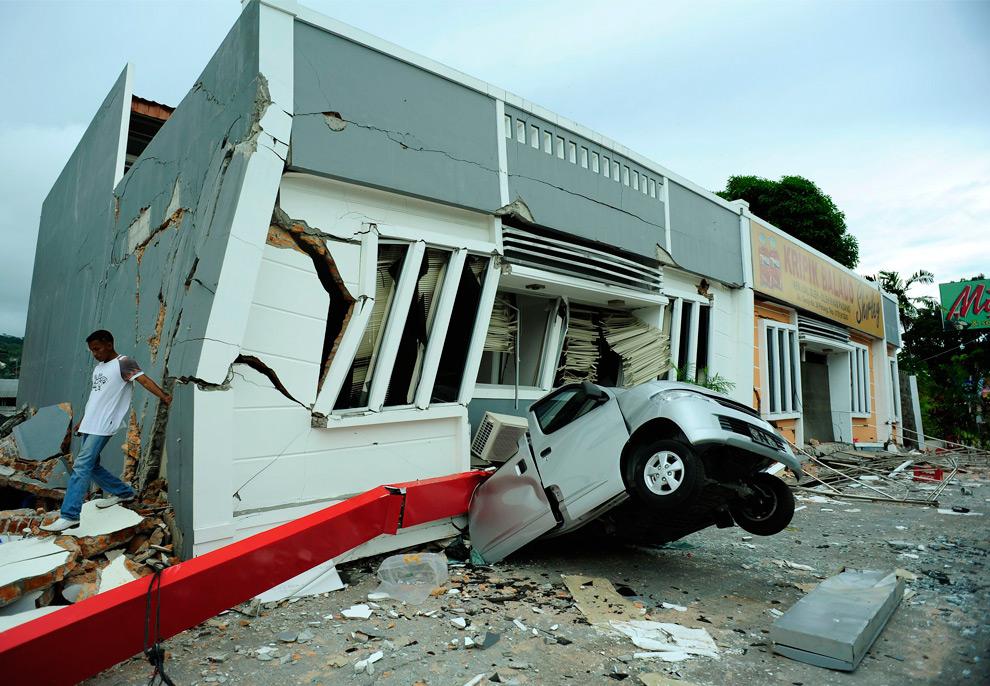 6. Мужчина уходит от полуразрушенного здания, упавшего на автомобиль, после землетрясения в центре Паданга в провинции Западная Суматра 3 октября 2009 года. (REUTERS/Dylan Martinez)