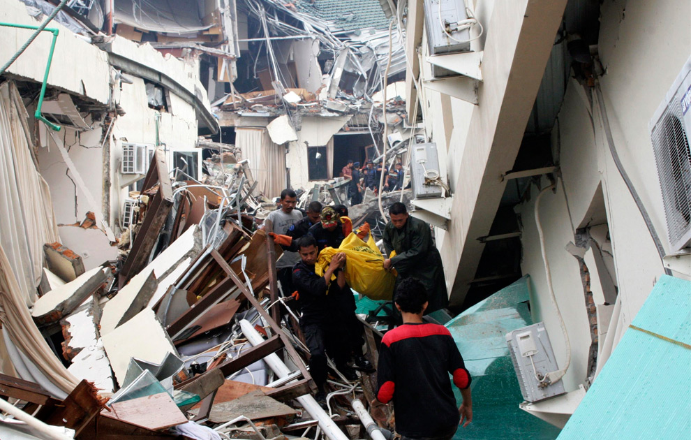 8. Солдаты и добровольцы выносят тело погибшего из разрушенного отеля в Паданге на Суматре 1 октября 2009 года. (REUTERS/Muhammad Fitrah/Singgalang Newspaper)