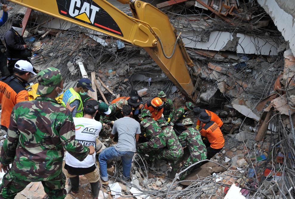 10. Команда спасателей из Индонезии достает из обломков здания тела погибших в Паданге 3 октября 2009 года. (ADEK BERRY/AFP/Getty Images)