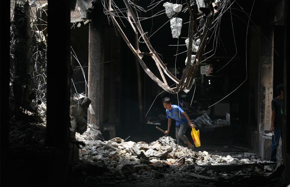 11. Мальчик осторожно идет под нависающими обломками бывшего рынка в воскресенье 4 октября 2009 года в Паданге, Индонезия. (AP Photo/Binsar Bakkara)